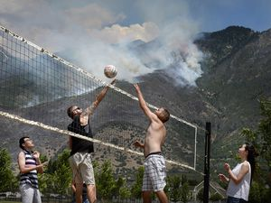Scott Sommerdorf      The Salt Lake Tribune  The Victor family plays volleyball as aerial crews fight the fires being driven uphill as seen from Creekside Park in Alpine, Sunday, July 16, 2017.