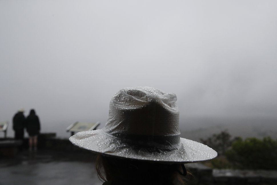 Raindrops sit on the plastic cover of a park ranger's hat outside the Jaggar Museum overlooking Kilauea's summit crater in Volcanoes National Park, Hawaii, Thursday, May 10, 2018. The park is closing Friday due to the threat of an explosive volcanic eruption. (AP Photo/Jae C. Hong)