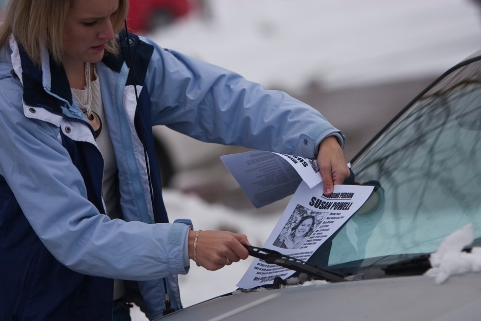 (Chris Detrick | Tribune file photo) A woman places missing-person fliers of Susan Powell on cars in a Smith's parking lot Saturday, Dec. 12, 2009.