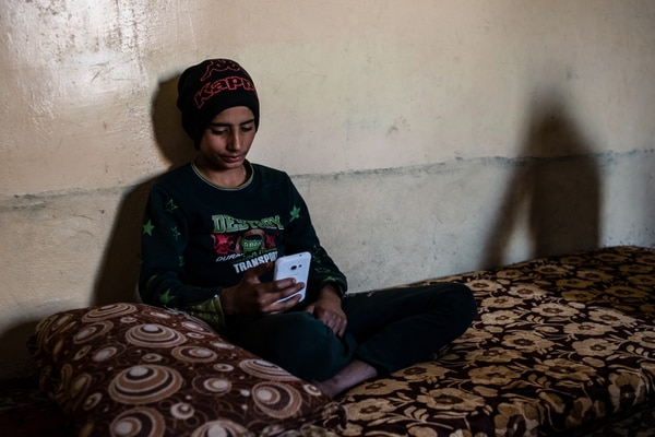 (Alex Potter | The Washington Post) Ahmed Jassim sits inside his home in Qayyarah, Iraq, scrolling through his Facebook page.