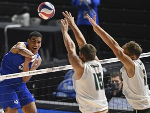 (David Dermer | AP) BYU's Gabi Garcia Fernandez (5) hits the ball as Hawaii's Patrick Gasman (15) and Jakob Thelle (10) go for a block during the NCAA men's volleyball championship match Saturday, May 8, 2021, in Columbus, Ohio. Hawaii swept BYU to win the title.