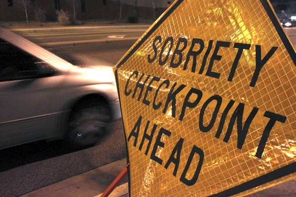 """FILE - In this Dec. 29, 2011 file photo, a car approaches a sobriety checkpoint set up along a busy street in Albuquerque, N.M. A prestigious scientific panel is recommending that states significantly lower their drunken driving thresholds as part of a blueprint to eliminate the """"entirely preventable"""" 10,000 alcohol-impaired driving deaths in the United States each year. (AP Photo/Susan Montoya Bryan)"""