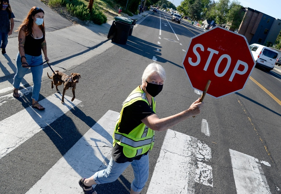 (Francisco Kjolseth | The Salt Lake Tribune) Christy Smith who has been a crossing guard for 33-years at Parkside Elementary in Murray, helps students and their parents cross Vine Street safely in Murray for the first day of school on Monday, August, 17, 2020. Murray is the first school district in the state to open.