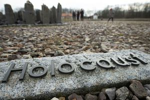 """(AP Photo/Jens Meyer, file) In this Monday, Jan. 27, 2020, photo, people walk behind the writing """"Holocaust"""" during the international Holocaust remembrance day in the former Nazi concentration camp Buchenwald near Weimar, Germany."""