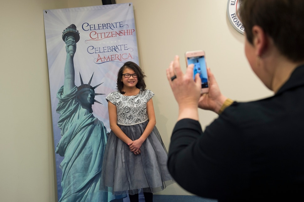 (Scott Sommerdorf | The Salt Lake Tribune) Lachlan Murray smiles as her mother Rose makes a photo of her prior to a ceremony in recognition of children who have obtained citizenship through their parents, Thursday, December 28, 2017. Some children were adopted by U.S. citizen parents; others derived citizenship when their immigrant parents became naturalized citizens.