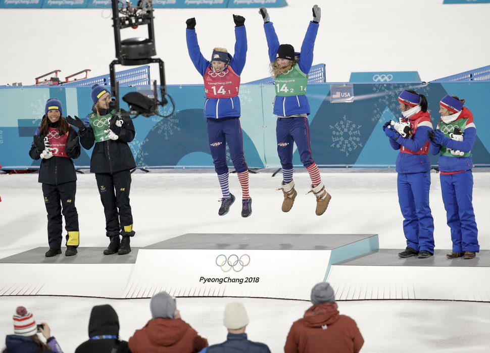 Gold medal winners Kikkan Randall, of the United States, and Jessica Diggins are flanked by silver medal winners Stina Nilsson, of Sweden, and Charlotte Kalla, left, and bronze medal winners Marit Bjoergen, of Norway, and Maiken Caspersen Falla during the venue ceremony after women's team sprint freestyle cross-country skiing final at the 2018 Winter Olympics in Pyeongchang, South Korea, Wednesday, Feb. 21, 2018. (AP Photo/Dmitri Lovetsky)