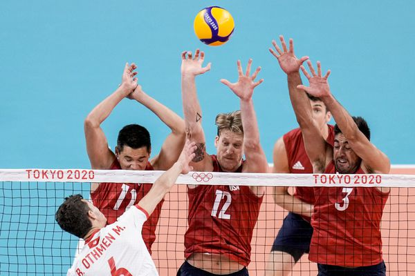 (Manu Fernandez | AP) Tunisia's Mohamed Ali Ben Othmen Miladi, left, spikes the ball over United States' Taylor Sander (3) and teammates during a men's volleyball preliminary round pool B match between United States and Tunisia at the 2020 Summer Olympics, Wednesday, July 28, 2021, in Tokyo.