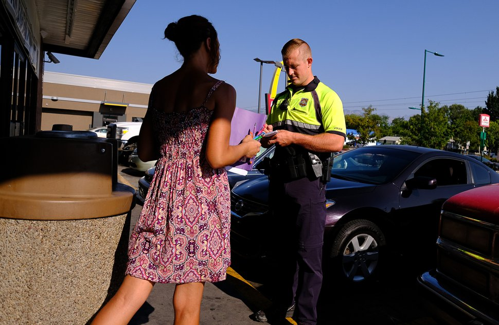 (Francisco Kjolseth | The Salt Lake Tribune) Officer Wyatt Sackett questions a woman known to have engaged in prostitution as she loiters in front of a convenience store along North Temple in Salt Lake City on Wednesday, Aug. 8, 2018. Members of the west side policing bicycle squad patrol Glendale and Rose Park with an emphasis along North Temple, where they have seen an increase in criminal activity following Operation Rio Grande, now nearing the halfway mark.