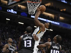 Utah Jazz's Hassan Whiteside scores a basket in front of Sacramento Kings' De'Aaron Fox, left, Triston Thompson and Harrison Barnes during the second half of an NBA basketball game in Sacramento, Calif., Friday, Oct. 22, 2021. The Jazz won 110-101. (AP Photo/José Luis Villegas)