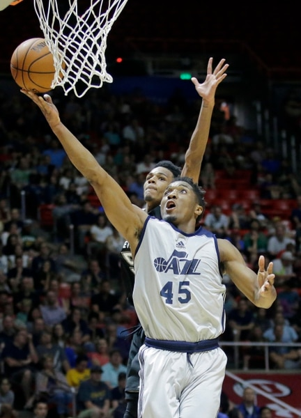 Utah Jazz guard Donovan Mitchell (45) lays the ball up as San Antonio Spurs guard Dejounte Murray, rear, defends during the first half of an NBA summer league basketball game Monday, July 3, 2017, in Salt Lake City. (AP Photo/Rick Bowmer)