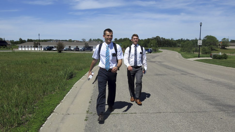(John Enger | Minnesota Public Radio) In this June 13, 2018 photo, Tanner Smedley and Joseph Smith head into Detroit Lakes, Minn., on foot for an afternoon of door knocking in Detroit Lake, Minn. Smedley and Smith both 19 from Utah, are part way through into their two-year Mormon mission. They have spent most of that mission assigned to Detroit Lakes.
