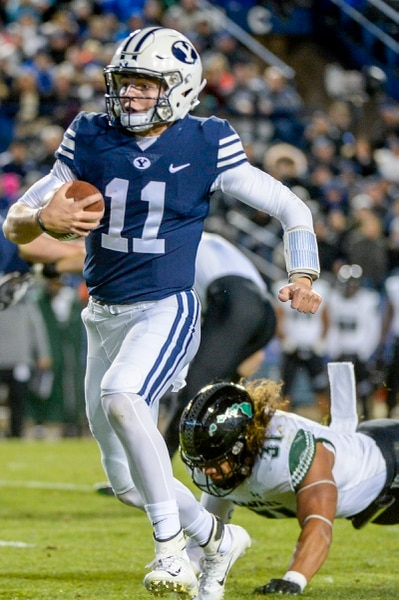 Leah Hogsten | The Salt Lake Tribune Brigham Young Cougars quarterback Zach Wilson slips past Hawaii linebacker Jahlani Tavai (31) on his touchdown run as Brigham Young University hosts Hawaii at Lavell Edwards Stadium in Provo, Saturday Oct. 13, 2018.