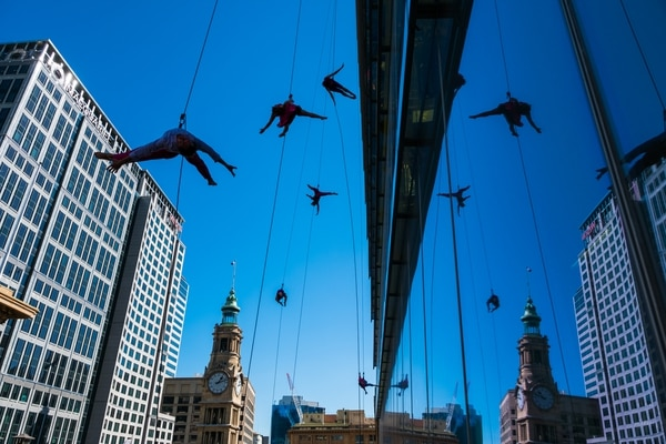 """(Photo courtesy of Basil Tsimoyianis) Oakland, Calif.-based """"vertical dance"""" company BANDALOOP performs in Sydney, Australia. The company will be appearing at the Utah Arts Festival June 21-24 and will perform twice daily (5:30 and 7 p.m.) on the six-story library glass wall above the reflecting pool."""