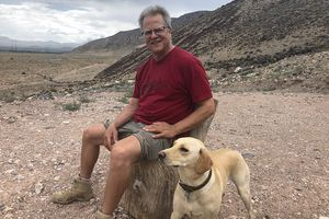 """""""Mystic Mike"""" Ginsburg sits with his dog, Stella, on bluff overlooking his property near Monroe, Utah, where the Mystic Hot Springs owner plans to build an art installation that could be seen from Interstate 70. It's a project that started thanks to rumors he was bringing Antifa to town to cause problems last Pioneer Day."""