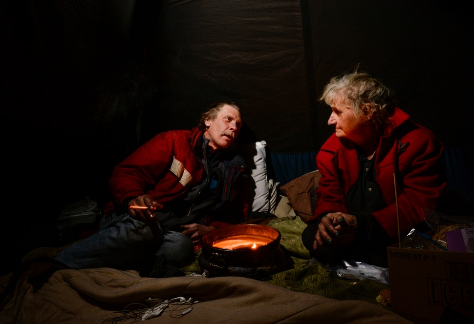 (Leah Hogsten | The Salt Lake Tribune) Ron Barrett, 55, and his wife Katherine Barrett, 54, who are homeless try to stay warm in their tent from the meager heat from a ceramic pot filled with candle wax. Their cold hands are blacken by the soot rising from the burning candle on a night that temperatures dropped to 12 degrees in Salt Lake City. It's crazy, you gotta be able to have a sense of humor, said Ron Barrett, 55, of the life circumstances that resulted in life on the streets for he and Katherine since 2017. The Barretts are trying to find housing through a Shelter Plus Care housing voucher through the Salt Lake City Housing Authority. The couple says they refuse to stay in the state's largest homeless shelter, The Road Home on Rio Grande Street, because of past threats of violence from other residents.