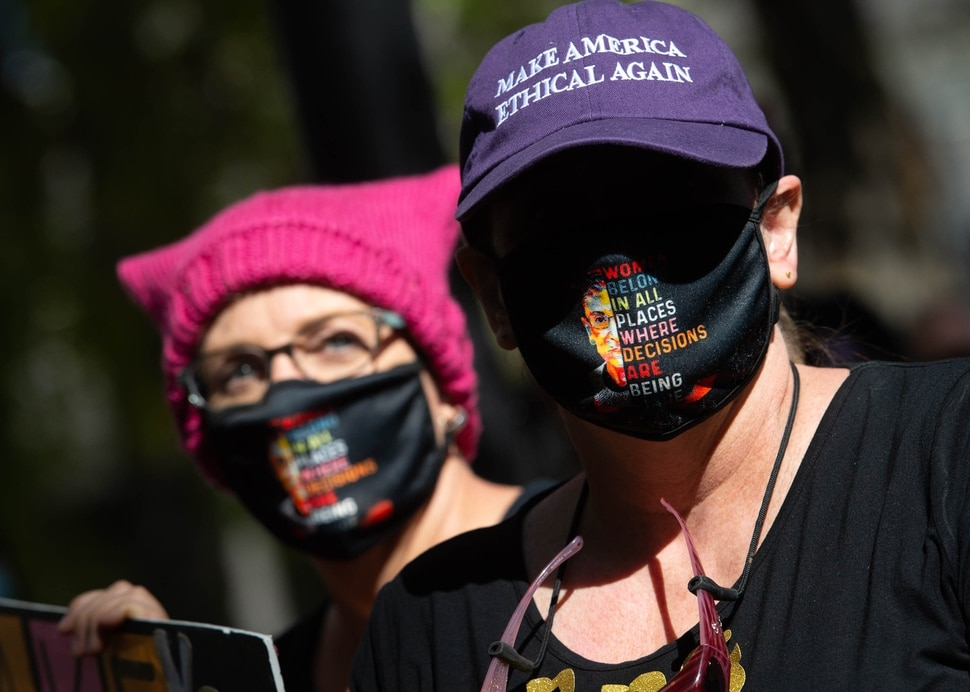 (Francisco Kjolseth | The Salt Lake Tribune) Sisters Laura, left, and Sarah Bush, listen to speakers at Salt Lake City Hall alongside demonstrators gathered for one of the Women's March rallies happening in Washington D.C. and around the country on Saturday, Oct. 17, 2020, to signal their opposition to President Donald Trump and his agenda, including his push to fill the seat of late Supreme Court Justice Ruth Bader Ginsburg before election day.