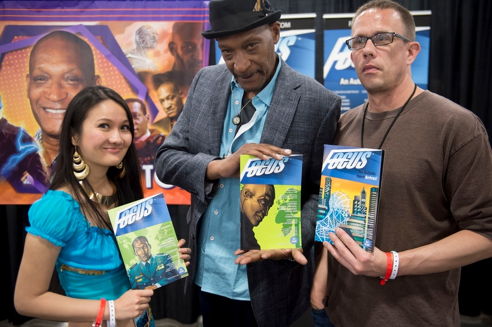 (Jeremy Harmon | The Salt Lake Tribune) Yvonne Wan, Tony Todd and Douglas Hebert pose with copies of Focus creator of the comic book Focus at Fan X in Salt Lake City on April 19, 2019. The comic book tells the story of a super hero with autism.