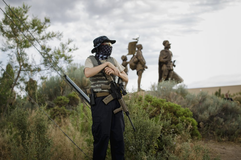 An armed militia member from The New Mexico Civil Guard stands by the statue of Juan de Oñate in Albuquerque, N.M. on June 15, 2020. The agitation against honoring Juan de Oñate reflects a tension that has long festered between Native Americans and Hispanics over Spain's conquest of New Mexico more than four centuries ago. (Adria Malcolm/The New York Times)