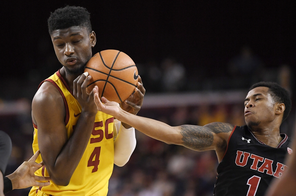 Utah guard Justin Bibbins, right, reaches in on Southern California forward Chimezie Metu during the second half of an NCAA college basketball game, Sunday, Jan. 14, 2018, in Los Angeles. USC won 84-67. (AP Photo/Mark J. Terrill)