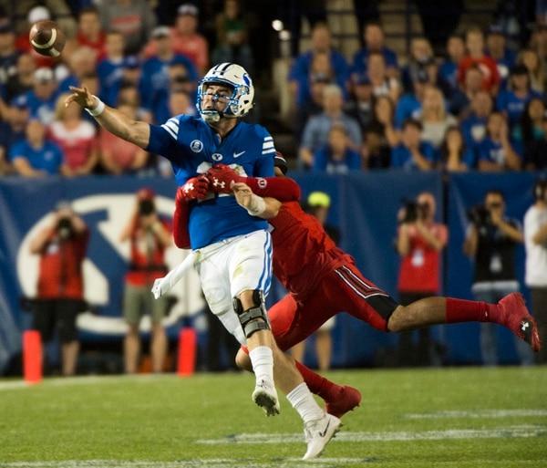 (Rick Egan   The Salt Lake Tribune) Brigham Young Cougars quarterback Tanner Mangum (12) is chased by Utah Utes defensive end Caleb Repp (47), football action BYU vs Utah, at Lavell Edwards Stadium in Provo, Saturday, September 9, 2017.