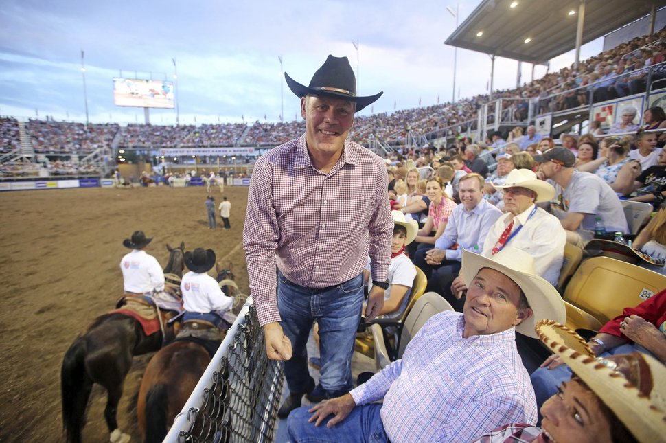 U.S. Interior Secretary Ryan Zinke, center, stands by Utah Gov. Gary Herbert during the Days of '47 Rodeo, on the Utah holiday Pioneer Day, Tuesday, July 24, 2018, in Salt Lake City. It's one of several events on the Pioneer Day holiday that celebrates the arrival of Mormon pioneers in the Salt Lake Valley. (AP Photo/Rick Bowmer)