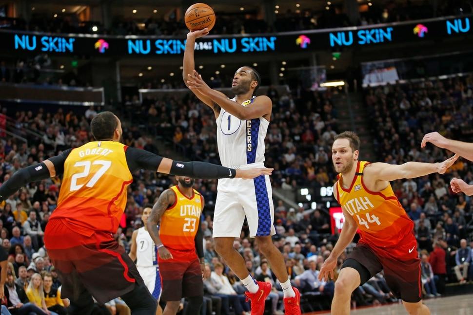 Indiana Pacers forward T.J. Warren (1) shoots as Utah Jazz's Rudy Gobert (27) and Bojan Bogdanovic (44) defend in the first half of an NBA basketball game Monday, Jan. 20, 2020, in Salt Lake City. (AP Photo/Rick Bowmer)
