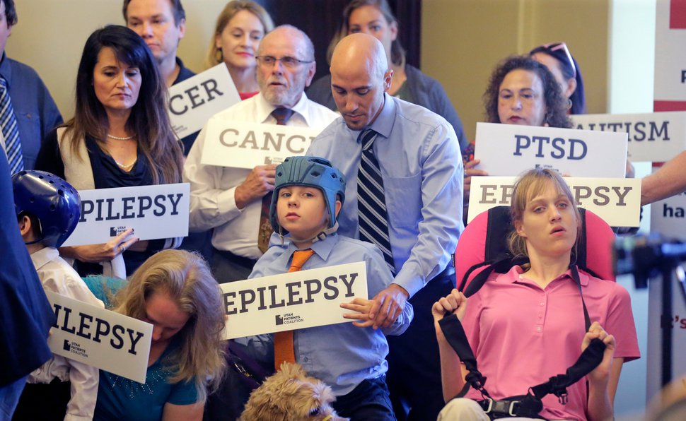 FILE - In this June 26, 2017, file photo, Davis Cromar, center, holds his son Holden, 10, who suffers from epilepsy, while standing with other patients, caregivers and supporters during the Utah Patients Coalition news conference, in Salt Lake City. Voters in the deep red states of Utah and Oklahoma will have a chance to legalize medical marijuana through ballot initiatives that offer the latest illustration of how quickly the United States is leaving behind taboos about the drug. (AP Photo/Rick Bowmer, File)