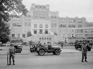 FILE - In this Sept. 26, 1957 file photo, members of the 101st Airborne Division take up positions outside Central High School in Little Rock, Ark. The troopers are on duty to enforce integration at the school. Officials said Wednesday, July 26, 2017, that newly unveiled plans to commemorate the 60th anniversary of nine African-American students desegregating Little Rock Central High School will reflect on the progress made in educating students of diverse backgrounds. (AP Photo, File)