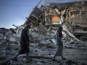 (AP Photo/Khalil Hamra) Palestinians walk next to the remains of a destroyed 15 story building after being hit by Israeli airstrikes on Gaza City, Thursday, May 13, 2021.