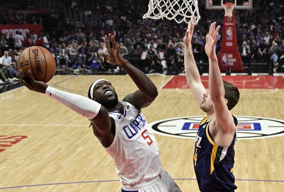 Los Angeles Clippers forward Montrezl Harrell, left, shoots as Utah Jazz forward Tyler Cavanaugh defends during the first half of an NBA basketball game Wednesday, April 10, 2019, in Los Angeles. (AP Photo/Mark J. Terrill)