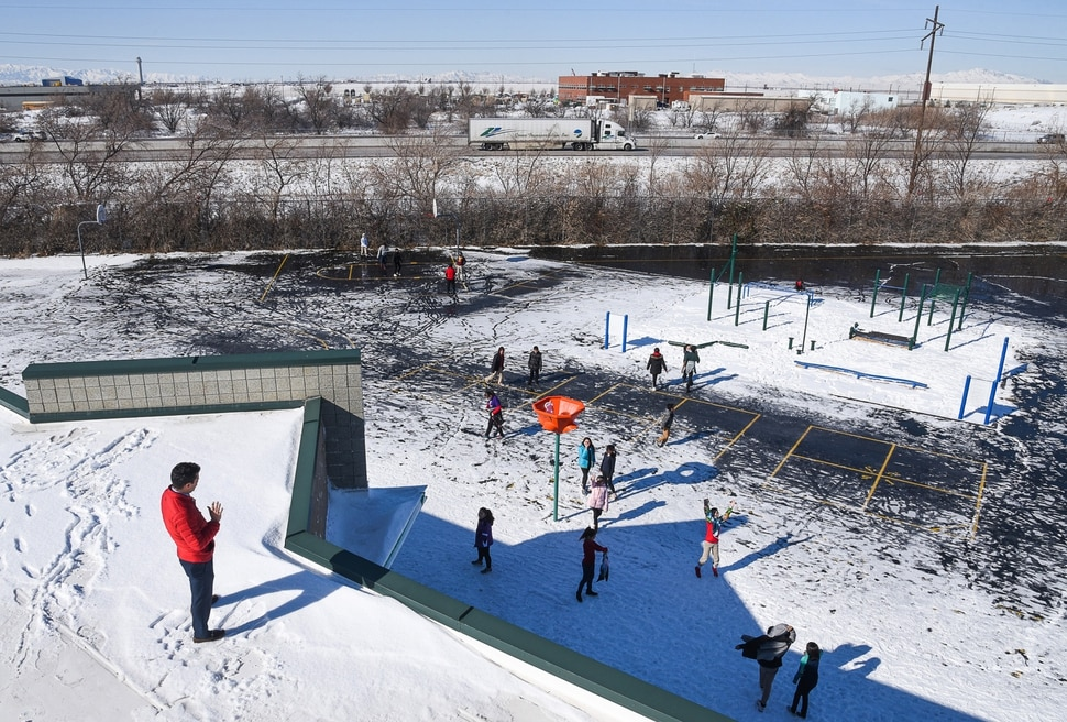 (Francisco Kjolseth | The Salt Lake Tribune) North Star Elementary principal Nathan Elkins gets an elevated view of students during recess as they play adjacent to I-215 on Monday, Feb. 11, 2019. With 530 students in Pre-K through 6th grade, it is one of the closest schools to the planned inland port development, located less than a mile away. The inland port, a massive development planed for Salt Lake City's westernmost area is cause for concern for the Salt Lake City School District through possible impacts in air quality and students, who they already have to keep inside from recess on bad air days.