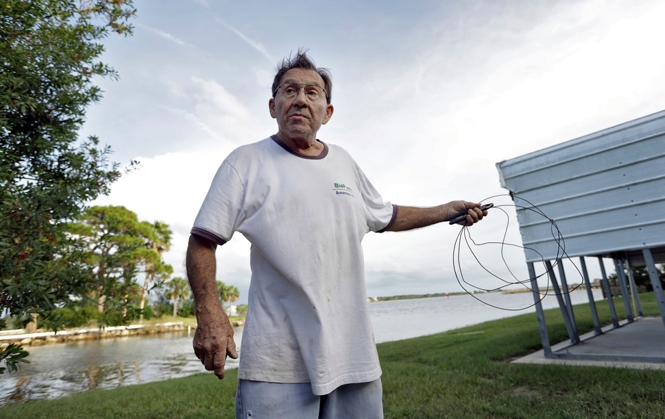 (Chris O'Meara | The Associated Press) Robert Sandousky gestures as he holds up some wire he plans on using to repair one of his fences from storm debris at his home Tuesday, Oct. 9, 2018, in Keaton Beach, Fla. Sandousky has ridden out several storms since he moved to the area some 40 years ago. Hurricane Michael continues to churn in the Gulf of Mexico heading for the Florida panhandle.