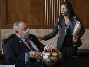 (Jim Watson | Pool via AP) Rep. Deb Haaland, D-N.M.,  delivers a gift to Rep. Don Young, R-Alaska, before the start of the Senate Committee on Energy and Natural Resources hearing on her nomination to be Interior secretary, Tuesday, Feb. 23, 2021 on Capitol Hill in Washington.