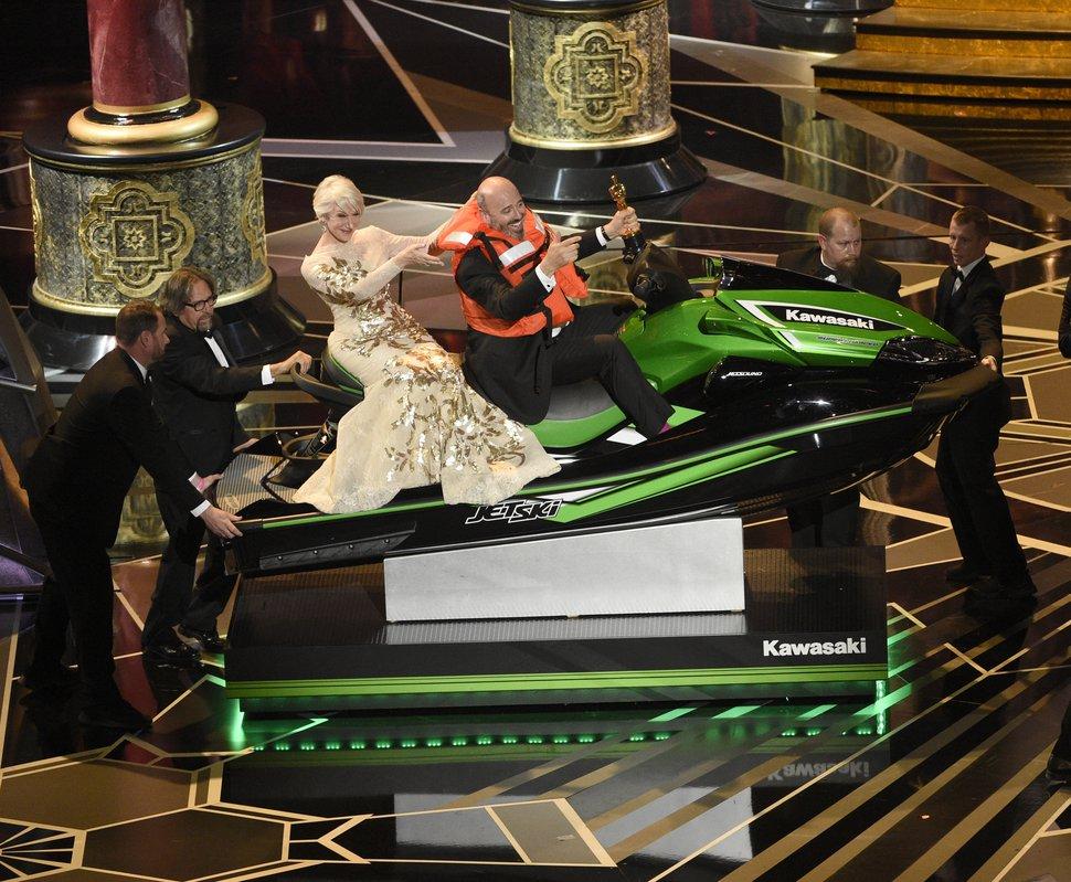 Helen Mirren, left, accompanies Mark Bridges, winner for the award for best costume design for