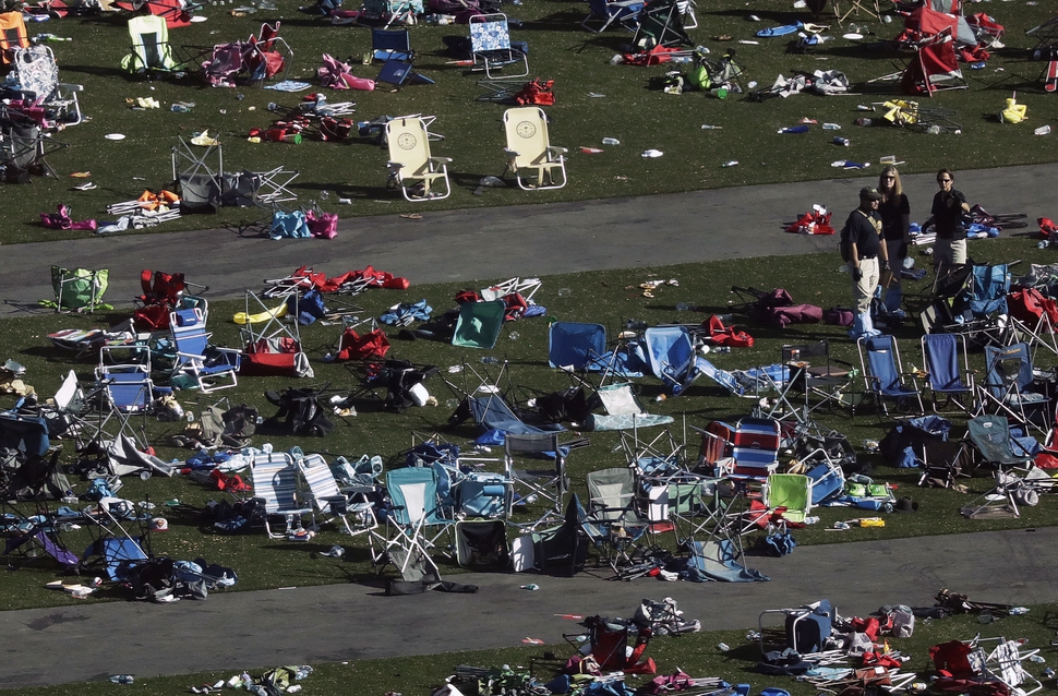 FILE - In this Oct. 3, 2017, file photo, investigators work among thousands of personal items at a festival grounds across the street from the Mandalay Bay Resort and Casino in Las Vegas. Friends and relatives of the victims and other concert-goers who survived returned Monday, Oct. 9, 2017, to reclaim baby strollers, shoes, phones, backpacks and purses left behind in the panic as they fled, at a Family Assistance Center at the Las Vegas Convention Center. (AP Photo/Marcio Jose Sanchez, File)