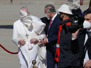 (Andrew Medichini | AP) A gust of wind blows Pope Francis's mantle as he stands by Iraqi Prime Minister Mustafa al-Kadhimi upon his arrival at Baghdad's international airport, Iraq, Friday, March 5, 2021. Pope Francis heads to Iraq on Friday to urge the country's dwindling number of Christians to stay put and help rebuild the country after years of war and persecution, brushing aside the coronavirus pandemic and security concerns.