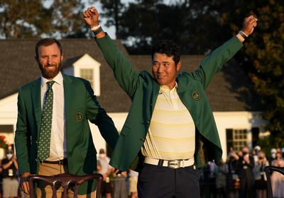 Hideki Matsuyama, of Japan, puts on the champion's green jacket after winning the Masters golf tournament as Dustin Johnson watches on Sunday, April 11, 2021, in Augusta, Ga. (AP Photo/David J. Phillip)