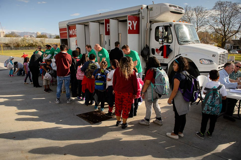 (Trent Nelson | Tribune file photo) Students at Jackson Elementary School in Salt Lake City pick up bags of food from the Utah Food Bank's mobile pantry on Nov. 2, 2017.