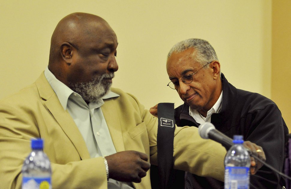 (Photo by Andy Carpenean/Laramie Boomerang) John Griffen, right, ties a black armband on the arm of his former teammate Mel Hamilton before a Black 14 panel discussion Nov. 3, 2009 in Laramie, Wyo.