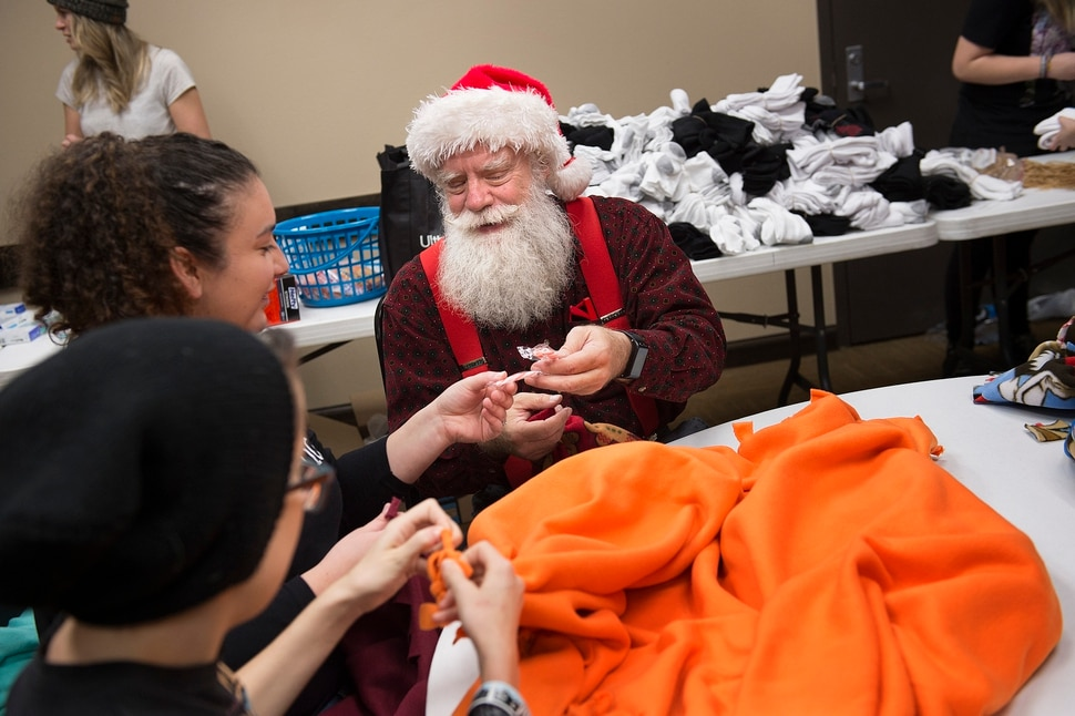 (Scott Sommerdorf | The Salt Lake Tribune) Fred Lane offers a fellow volunteer a candy cane during a break tying fleece tied blankets as Lady Gaga's Born This Way Foundation hosted an event at the Maverick Center to assemble care packages and write ÒKindness LettersÓ expressing support, hope, and love for LGBT+ youth experiencing homelessness in the area, Thursday, December 14, 2017.