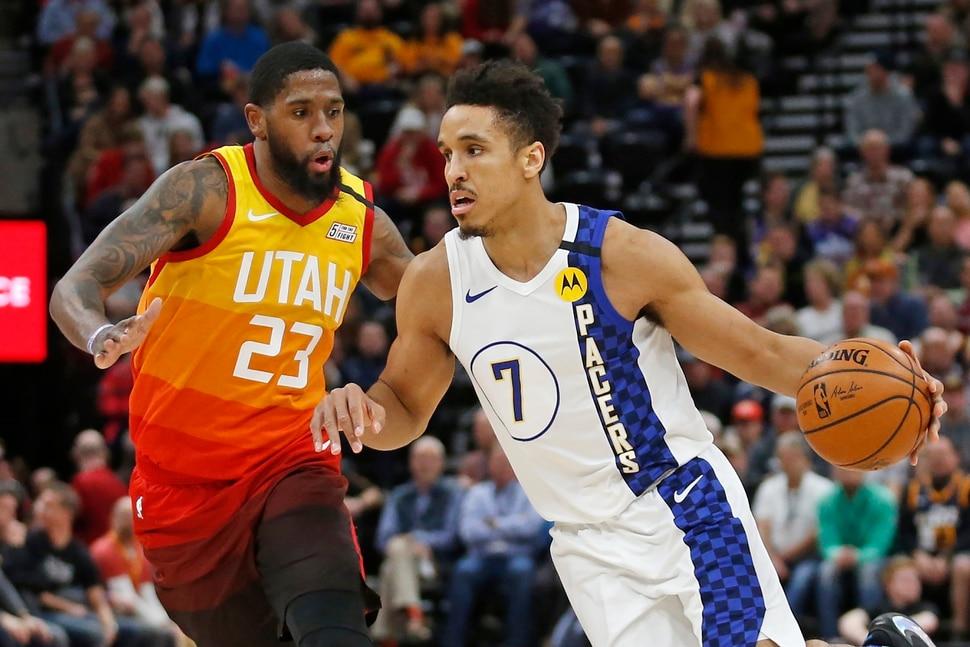 Indiana Pacers guard Malcolm Brogdon (7) drives around Utah Jazz forward Royce O'Neale (23) in the first half of an NBA basketball game Monday, Jan. 20, 2020, in Salt Lake City. (AP Photo/Rick Bowmer)