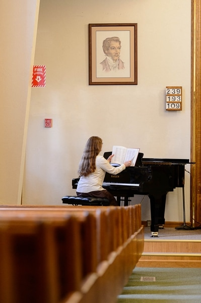 (Trent Nelson | The Salt Lake Tribune) Gail Wissenbach prepares to play a hymn on the piano during a Sacrament Meeting of the Pinesdale Second Ward, in Pinesdale, Mont.