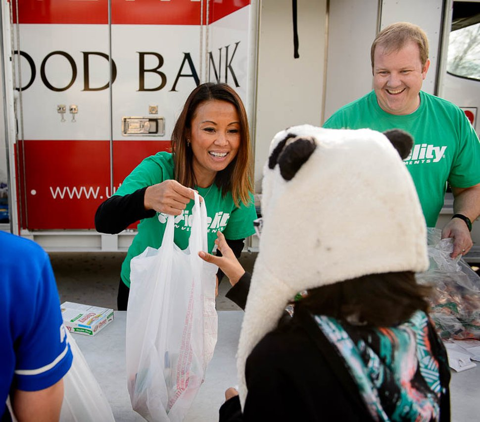 (Trent Nelson | The Salt Lake Tribune) June Wong and Justin Cornwall, volunteers from Fidelity Investments, hand out food to students at Jackson Elementary School in Salt Lake City as part of Utah Food Bank's mobile pantry, Thursday November 2, 2017.