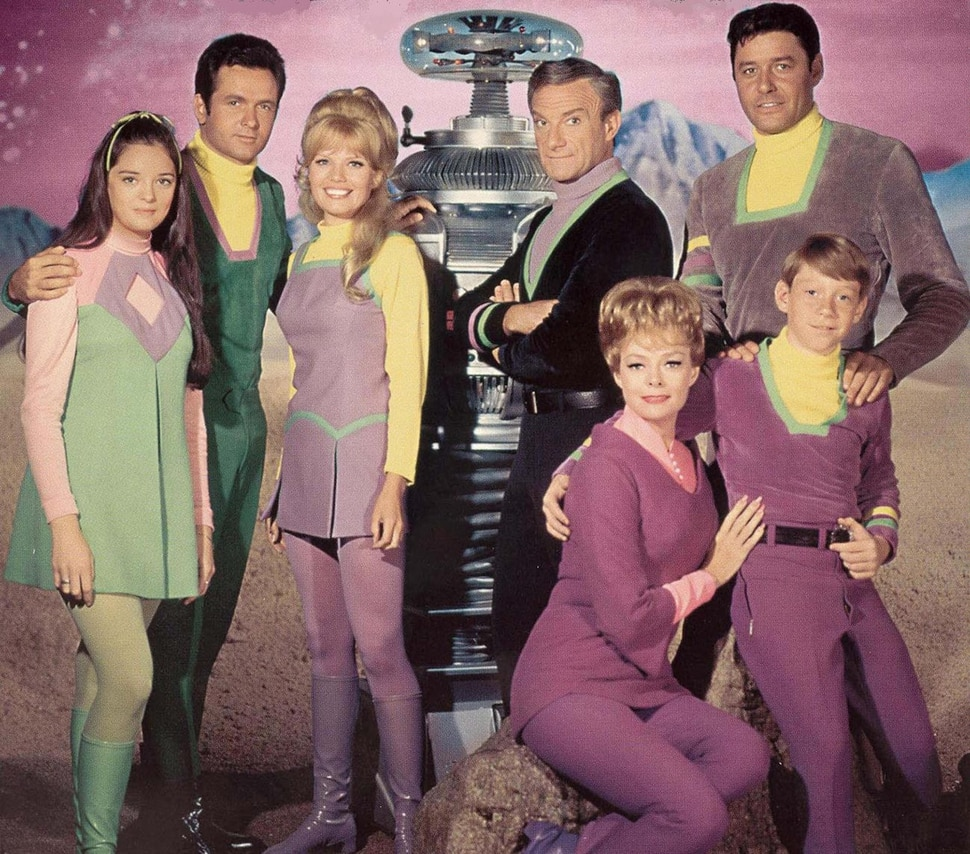 """(Photo courtesy of CBS) Angela Cartwright at Penny Robinson, Mark Goddard as Don West, Marta Kristen as Judy Robinson, the Robot, Jonathan Harris as Dr. Smith, June Lockhart as Maureen Robinson, Guy Williams as John Robinson, and Billy Mumy as Will Robinson in the original """"Lost in Space."""""""