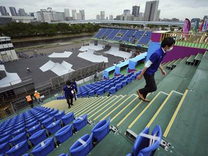 (Eugene Hoshiko   AP) Staffs walk at the grandstand as athletes compete during a Tokyo 2020 Olympic Game Cycling BMX Freestyle test event Monday, May 17, 2021, at the Olympic BMX Course of Ariake Urban Sports Park in Tokyo.