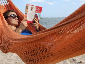 FILE - In this May 2, 2017, file photo, Kristiina Nurk, 34, enjoys a good book underneath the blue summer-like skies and weather as she vacations in Miami for a second day while on holiday. A new survey from The Associated Press-NORC Center for Public Affairs Research found that resting and relaxing is very or extremely important to three-fourths of Americans while on vacation. (Carl Juste/Miami Herald via AP, File)