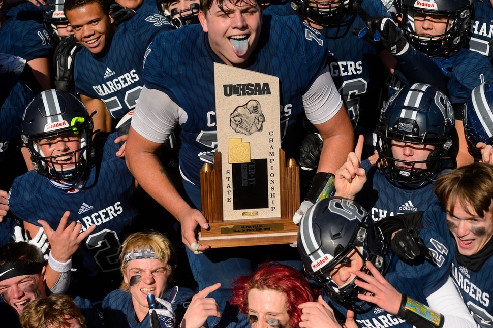(Trent Nelson | The Salt Lake Tribune) Corner Canyon's Jackson Light holds the trophy while celebrating with teammates after the 6A state football championship game against Lone Peak at Cedar Valley High School in Eagle Mountain on Friday, Nov. 20, 2020.