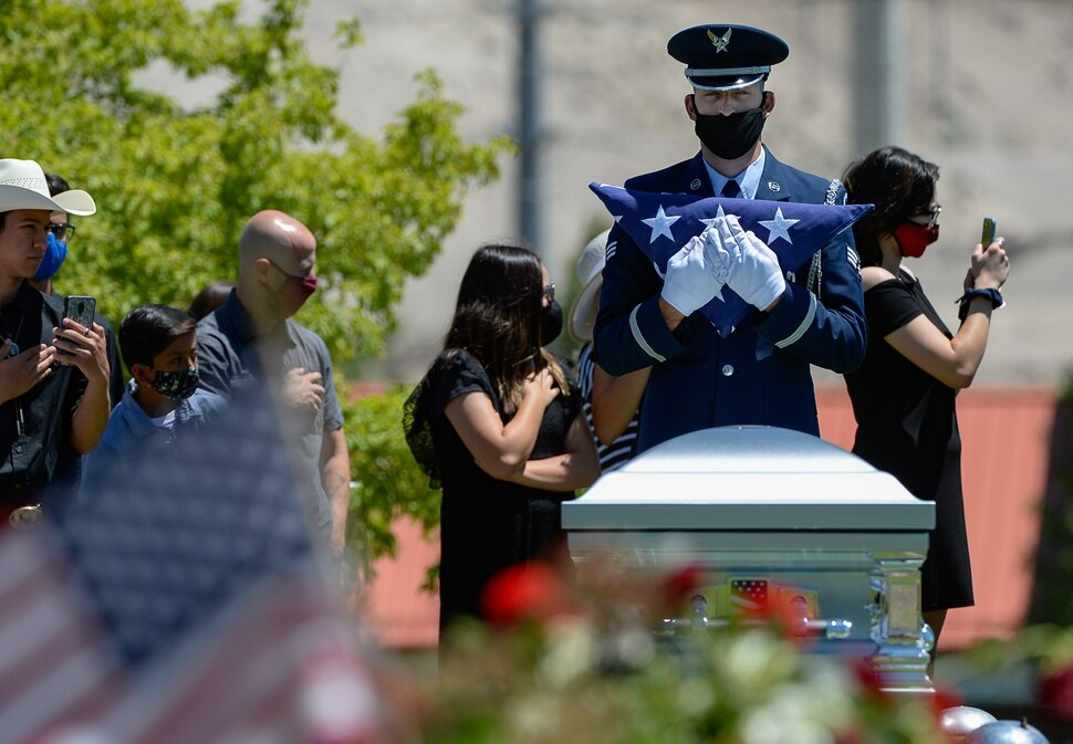 (Francisco Kjolseth | The Salt Lake Tribune ) Dallas Lynn Stevens is laid to rest at the Utah Veterans Cemetery in Bluffdale on Wednesday, June 24, 2020, as senior airman Trevor Thompson with the Hill Air Force Base color guard holds his flag.