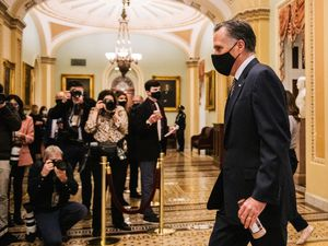 (Brandon Bell | The New York Times) Sen. Mitt Romney returns to the Senate Chamber after a break in the fourth day of former President Donald Trump's second Senate impeachment trial at the Capitol in Washington on Friday, Feb. 12, 2021.