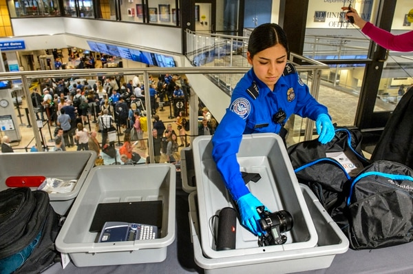 (Steve Griffin | The Salt Lake Tribune) TSA agent Suzanna Coria shows some of the electronic devises that need to be in their own bin under new stronger security procedures at the Salt Lake International Airport and five other Utah airports Thursday October 5, 2017.